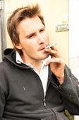 Un povero ragazzo giovane senzatetto fumare — Foto Stock