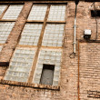 Angle shot of an abandoned industrial building with brick wall — Stock Photo