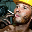 Worker covered in oil smoking - Stock Photo
