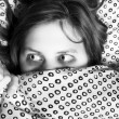 Young scared girl hiding under blanket — Stok fotoğraf