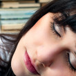 Stock Photo: Beautiful young school girl in library sleeping