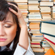 College girl holding her head against many books — Stock Photo #6299658