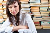 Beautiful young student girl in library — Stock Photo
