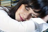 本の上で眠っている彼女の顔に笑みを浮かべて美しい学生少女 — ストック写真