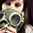 Beautiful girl is holding an old gasmask against dark background — Stock Photo