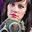 Portrait of a young woman holding her gasmask tight — Stock Photo