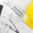 Construction plans with yellow helmet on it — Stock Photo