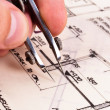 Compass in hand with construction plans - Stock Photo