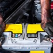 Engineer with oil on his hands holding a car battery tight - Stock Photo