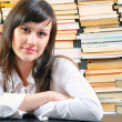 Young school girl with a lot of books against her — Stock Photo