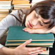 Young university student sleeping on books - Stock Photo