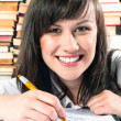 Happy student girl writing in notebook — Stock Photo