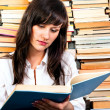Beautiful young student girl reading from a big book — Stock Photo #6733765