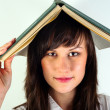 Beautiful young girl hiding under book — Stock Photo #6733777