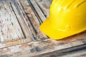Yellow helmet on burnt wooden log — Stock Photo