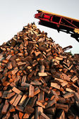 Firewood piled up with great machines — Stock Photo