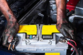 Engineer with oil on his hands holding a car battery tight — Stock Photo