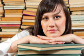 Portrait of a young student against piled up books — Stock Photo