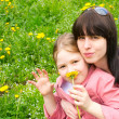 Mother and the daughter on a green meadow with dandelions — Stock Photo #5648676