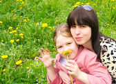 Mother and the daughter on a green meadow with dandelions — Stok fotoğraf