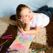 Stock Photo: The girl lies on a carpet and thoughtfully draws color pencils a picture