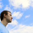 The young man looks at the blue sky — Stock Photo