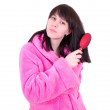The young woman in a dressing gown combs hair a hairbrush — Stock Photo