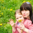 Mother and the daughter on a green meadow with dandelions — Stock Photo