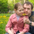 Stock Photo: The father and the daughter on a green meadow with dandelions