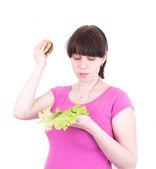 Mladá žena vyhodí hamburger drží salát — Stock fotografie