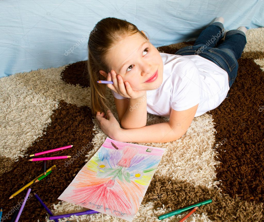 The girl lies on a carpet and thoughtfully draws color pencils a picture — Stock Photo #5667279