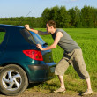 The man pushes the car in the field — Stock Photo