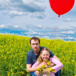 Girl with father and red balloon in meadow — Stock Photo #5972491