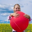 Girl with red balloon in meadow — Stock Photo #5972632