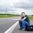 The young man sits pending on road with a suitcase — Stock Photo