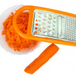 Grated carrots in a white plate, grater on the white isolated ba — Stok fotoğraf