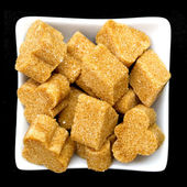 Brown sugar in a white bowl on black — Stock Photo