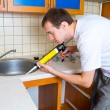 Plumber putting a silicone sealant to installing a kitchen sink — Stock Photo