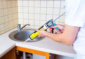 Těsnící pistole uvedení silikonový tmel k instalaci si kuchyň — Stock fotografie