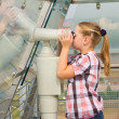 A girl looks through a telescope — Stock Photo