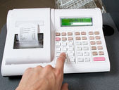 Hand and cash register — Stock Photo