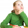 Little girl dreaming at the table on white — Stock Photo