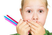 Little girl covers her mouth with her hands and holding a pencil — Stok fotoğraf