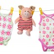 Stock Photo: Baby sleepers and pig on clothesline, studio isolated on whi