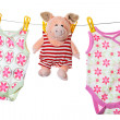 Baby sleepers and pig on the clothesline, studio isolated on whi - Stock Photo