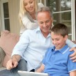 Stock Photo: Family sitting in couch with electronic tablet