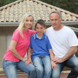 Family standing in front of their house — Stock Photo #5695144