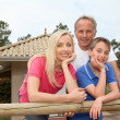 Family standing in front of their house — Stockfoto