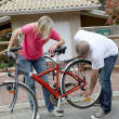 Couple checking bicycle — Stockfoto