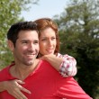 Man holding girlfriend on his back — Stock Photo